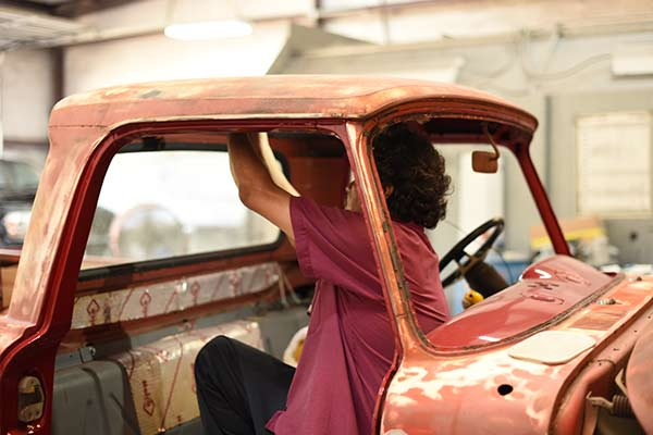 man installing new headliner in old truck